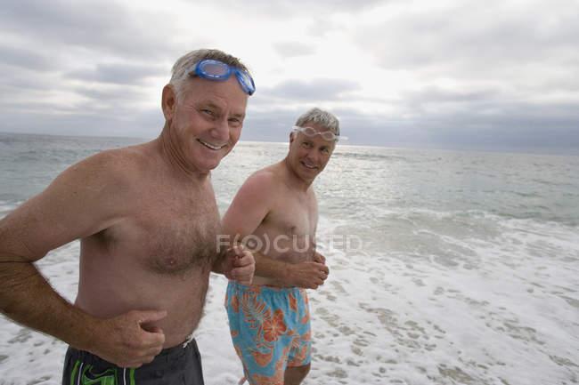 Uomini maturi in costume da bagno con il mare su priorità bassa ...