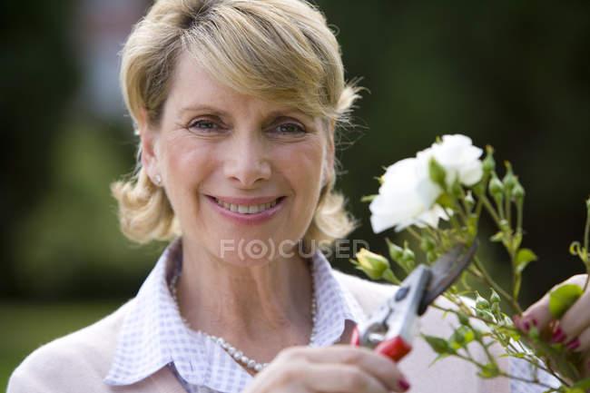 Vista frontal de bush de poda de mulher madura com tesouras de podar — Fotografia de Stock