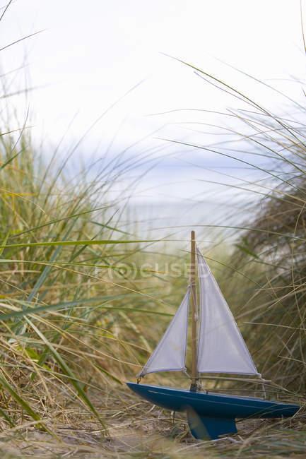 Barco de brinquedo na areia, na grama — Fotografia de Stock