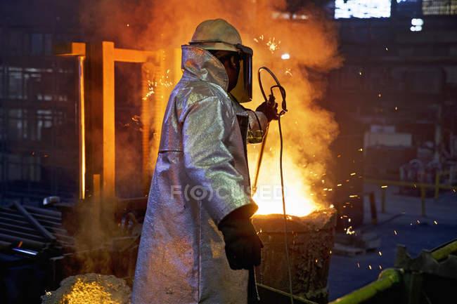 Gießerei Arbeiter Kontrollen Temperatur des geschmolzenen Metalls im Stahlwerk — Stockfoto