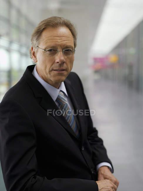 Businessman posing in corridor — Stock Photo