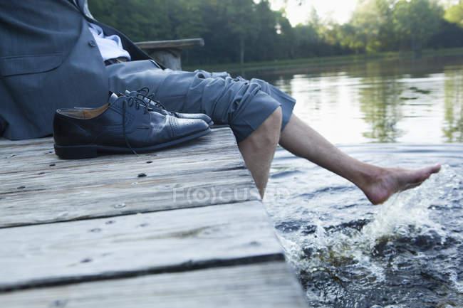 Homme assis sur la jetée au lac avec les pieds dans l'eau — Photo de stock