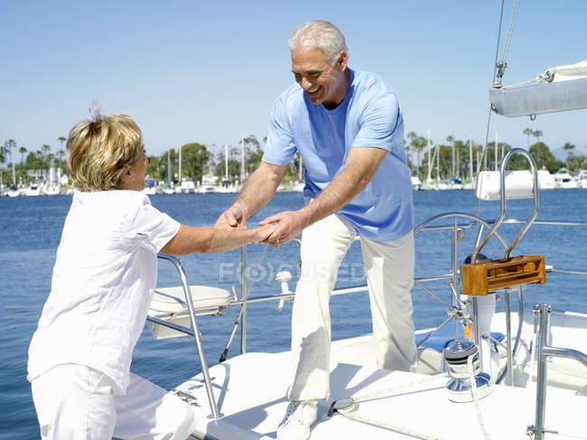 Senior man holding woman to help getting onto boat — Stock Photo