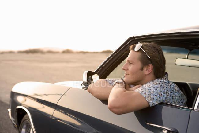 Молодий чоловік у автомобіля, дивиться вікно, вид збоку — стокове фото