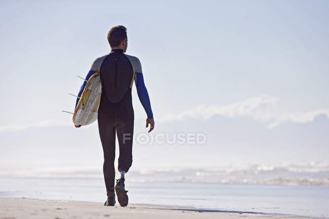 Rear view of surfer with artificial leg walking with surfboard on beach — Stock Photo