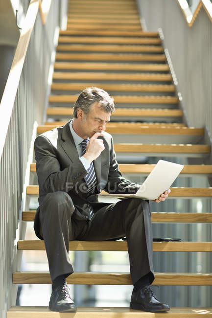 Businessman sitting on staircase looking at laptop — Stock Photo