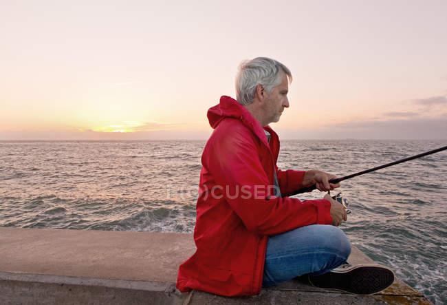 Reifer Mann Meer Angeln vom Steg Sonnenuntergang im Hintergrund — Stockfoto