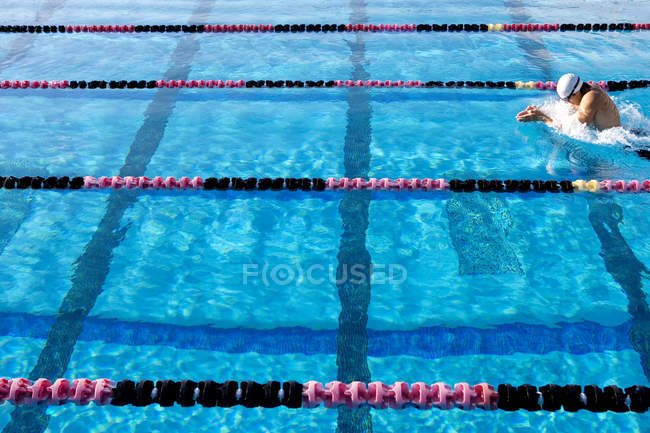 Young male sporstman swimming in lane in pool — Stock Photo
