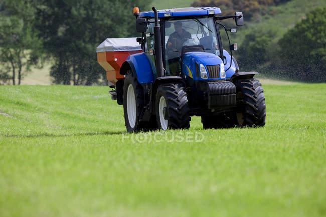 Épandage de produits dans le domaine de tracteur — Photo de stock