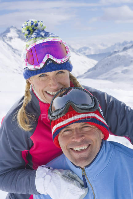 Closeup outdoor portrait of smiling couple wearing goggles and hugging at daytime, mountains background — Stock Photo