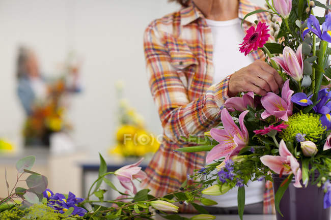 Woman putting flowers into floral arrangement in classroom — Stock Photo