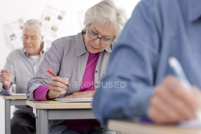 Adult students taking test in college during evening class — Stock Photo