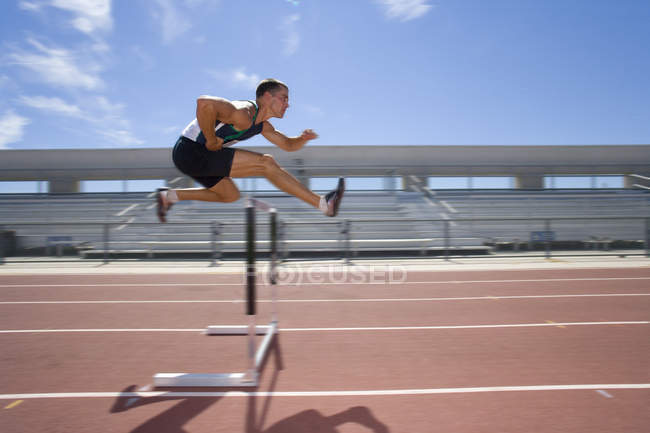 Male athlete jumping over jump (blurred motion) — Stock Photo