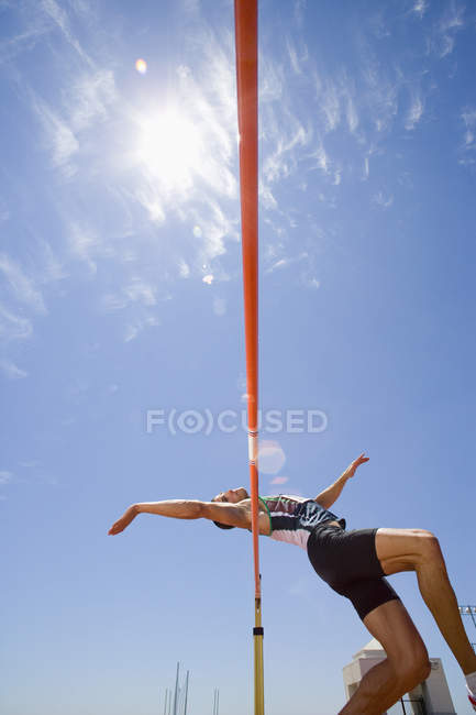 Young male athlete jumping over bar, low angle view (lens flare) — Stock Photo