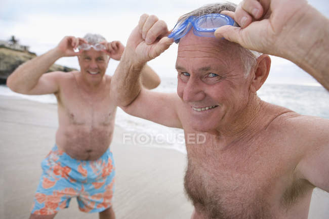 Mature men in swimming trunks adjusting goggles on beach — Stock Photo