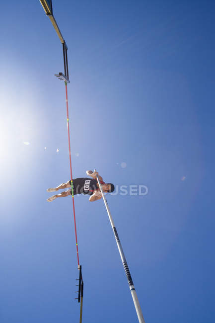 Pole vault athlete going over bar, low angle view (lens flare) — Stock Photo