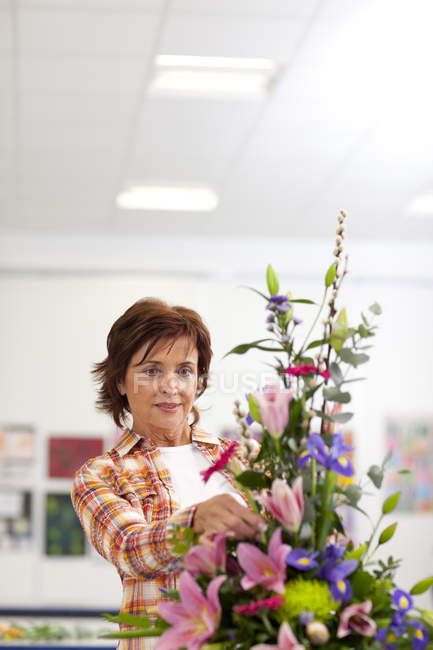 Serious woman putting flowers into floral arrangement in classroom — Stock Photo