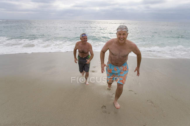 Smiling senior men in swimming trunks running from sea — Stock Photo