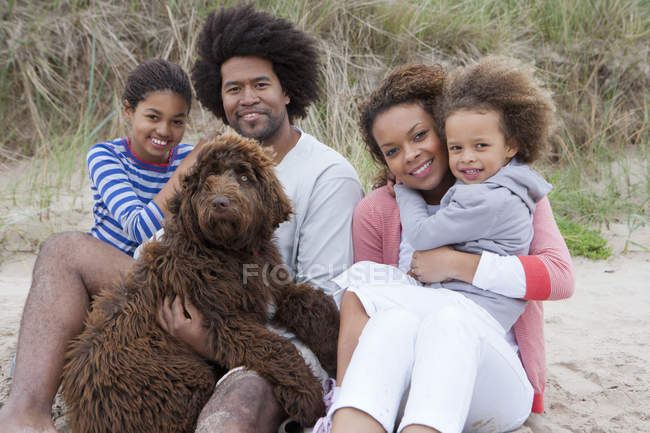 Portrait of mixed race family sitting on beach with dog — Stock Photo