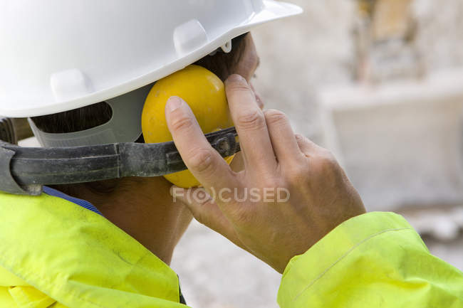Construction worker wearing ear protectors — Stock Photo