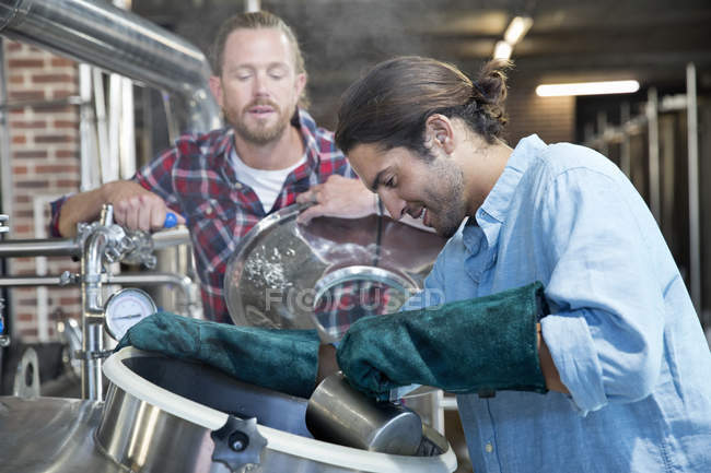 Brewery Workers Checking Fermentation Process In Steel Vat — Stock Photo