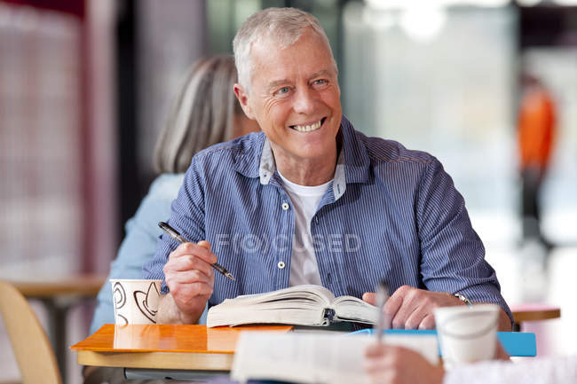 Smiling mature student writing in textbook and smiling — Stock Photo