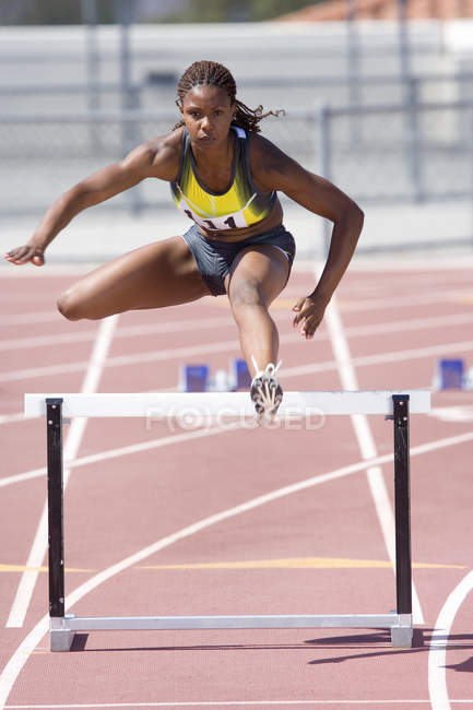 African female runner clearing hurdle — Stock Photo