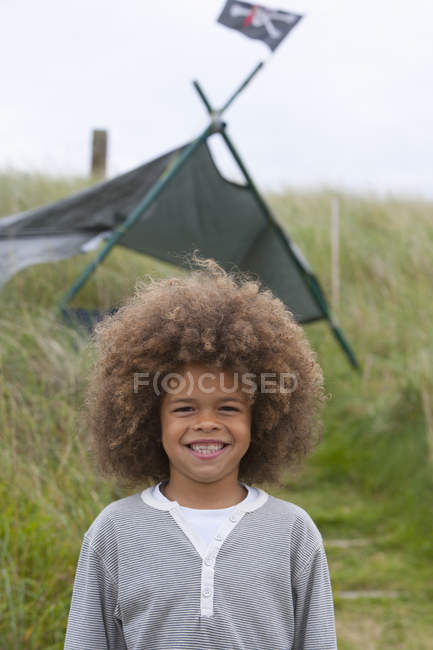 Happy mixed race boy standing next to tent — Stock Photo