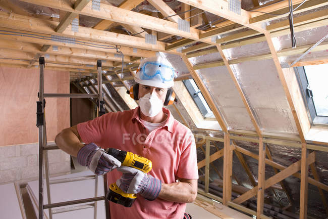 Worker holding drill and looking at camera — Stock Photo