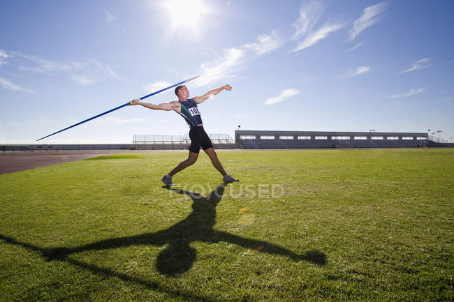 Male athlete preparing to throw javelin, low angle view (lens flare) — Stock Photo