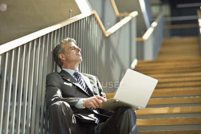 Businessman sitting on staircase with eyes closed holding laptop — Stock Photo
