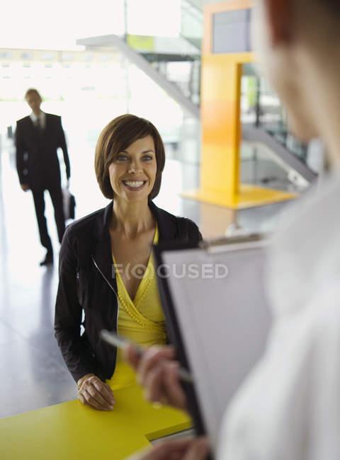 Предприниматель, улыбаясь в бюро информации — стоковое фото