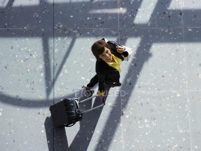 Бізнес-леді потягнувши валізу і дивлячись на камеру — стокове фото