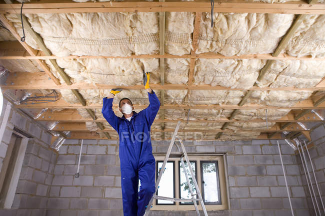 Man in coveralls and protective mask standing on ladder and installing ceiling — Stock Photo