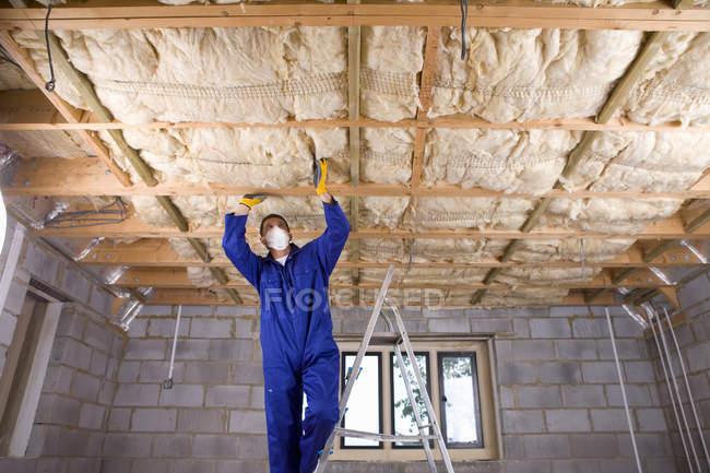 Hombre en overoles y máscara protectora permanente de escalera e instalación de techo - foto de stock