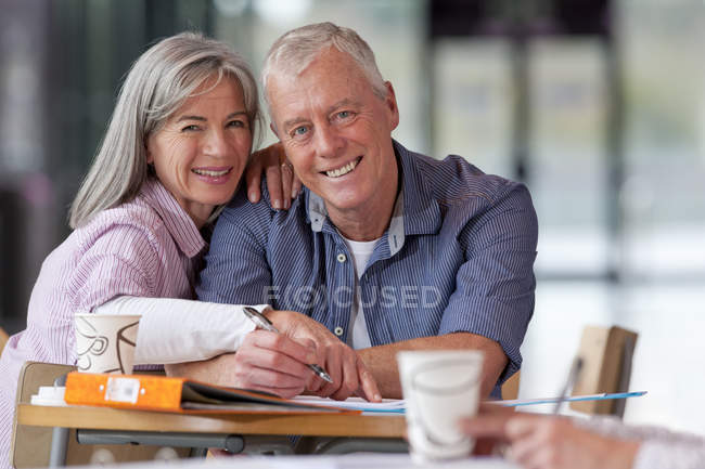 Smiling mature couple sitting at table and looking at camera while studying — Stock Photo