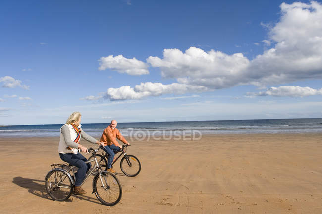 Senior couple cycling on beach, smiling at each other — Stock Photo
