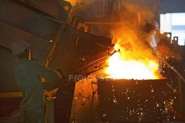 Trabajadores de ropa de protección verter Metal fundido en la fundición - foto de stock