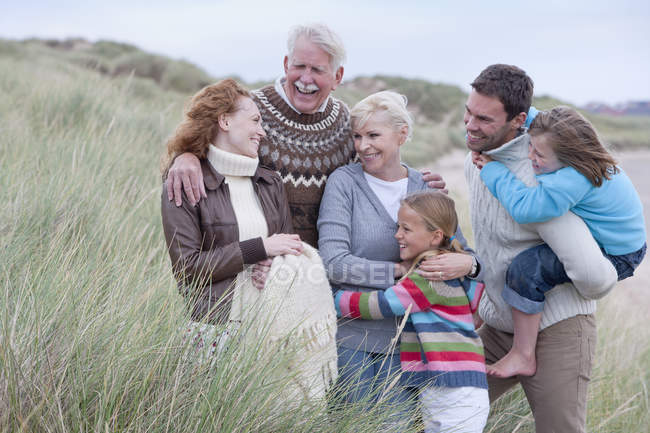 Multi generation family standing in grass near sand beach — Stock Photo