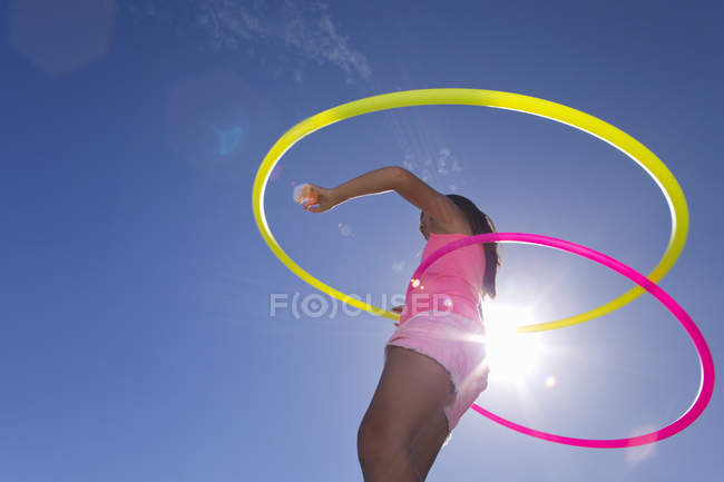 Vue faible angle de fille tourne deux cerceaux en plastique — Photo de stock
