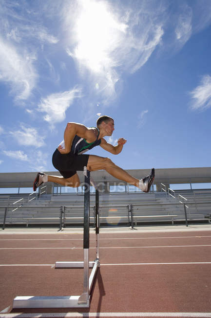 Male athlete jumping over hurdle, side view (lens flare) — Stock Photo