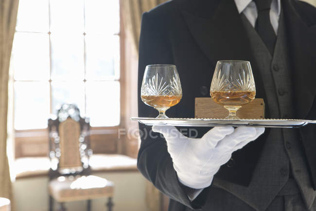 Butler with tray of drinks, mid section — Stock Photo