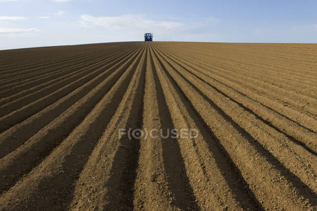 Ploughed field with tractor — Stock Photo