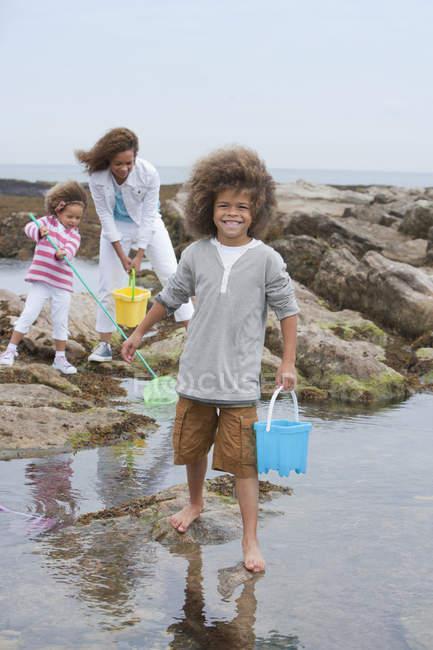 Madre y los niños de raza mixta explorar pozas - foto de stock