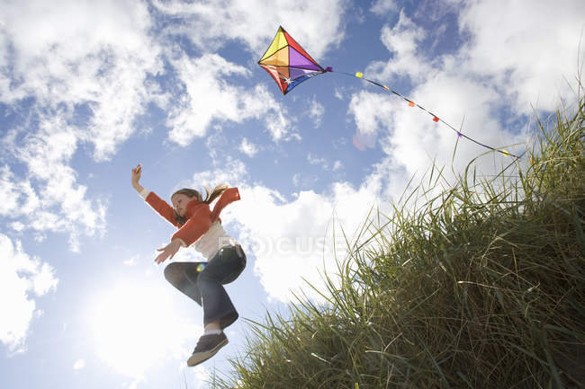 Niedrigen Winkel Ansicht des Mädchens abspringen Hügel Holding kite — Stockfoto