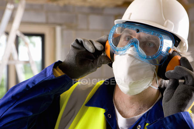 Construction man wearing hard hat with protective utensils — Stock Photo