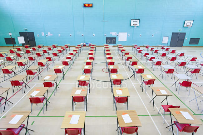 Rows of desks with test papers — Stock Photo
