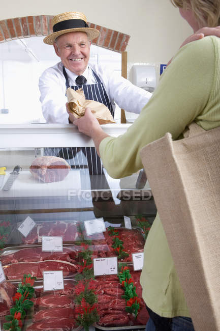 Butcher selling meat to customer — Stock Photo