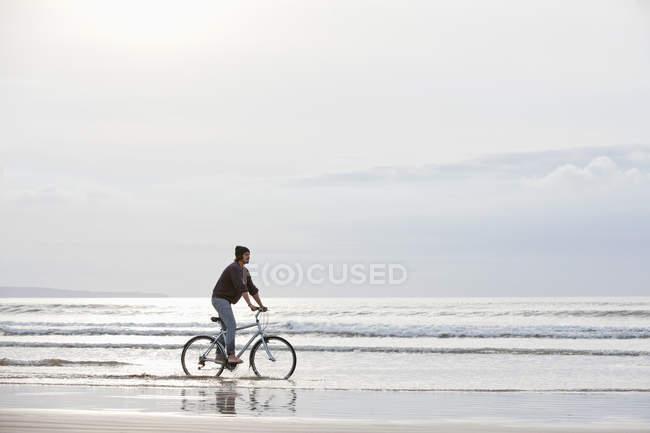 Vue éloignée de l'homme à vélo dans les brisants — Photo de stock