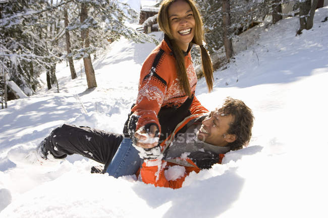 Vista frontal de la pareja de raza mixta, jugando en la nieve - foto de stock